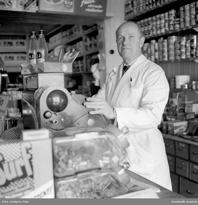 Livsmedelsbutik på Norrmalmsgatan 39. Här står butiksägaren Nils Olsson utanför butiken som först hans far A G Olsson och därefter han själv drev från 1920 fram till 1962. Bild 2 visar Nils Olsson vid kassaapparaten inne i butiken.