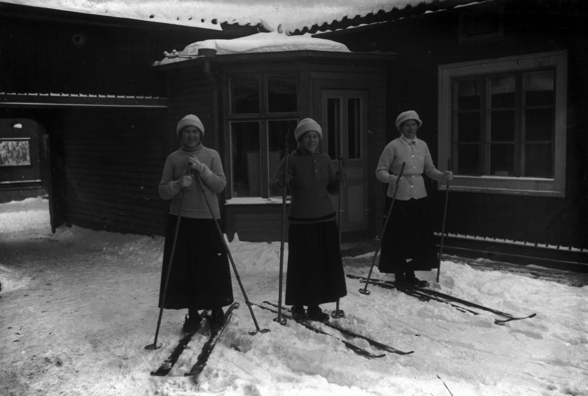 Tre unga kvinnor på skidor. I mitten Ester Pettersson (givarens faster).I bakgrunden skrädderiet.