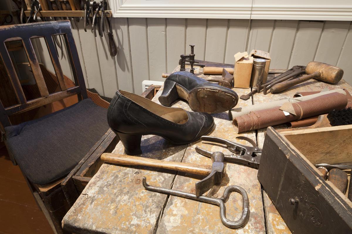 Forskjellige skomakerverktøy og et par damesko på et bord