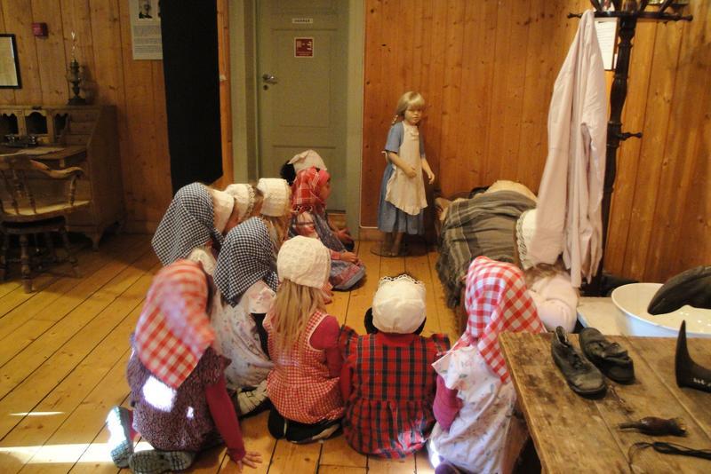 Barn sitter på gulvet i gammeldagse kostymer og lytter til historien om lille Maren og Skinnfell-Marja.