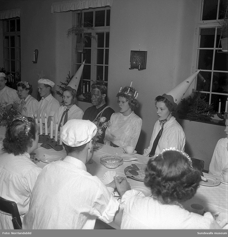"""Luciahögtid på Sidsjöns sjukhus 1950. Första bilden visar en tidig kaffestund för luciaföljet innan det var dags att tåga genom de olika avdelningarna. Från vänster: Ida Jacobsson, """"bagarn"""" Wikdahl, Barbro Svensson, """"sotarn"""" Henry Ledin, lucia Ulla Bild och Maj-Britt Svensson."""