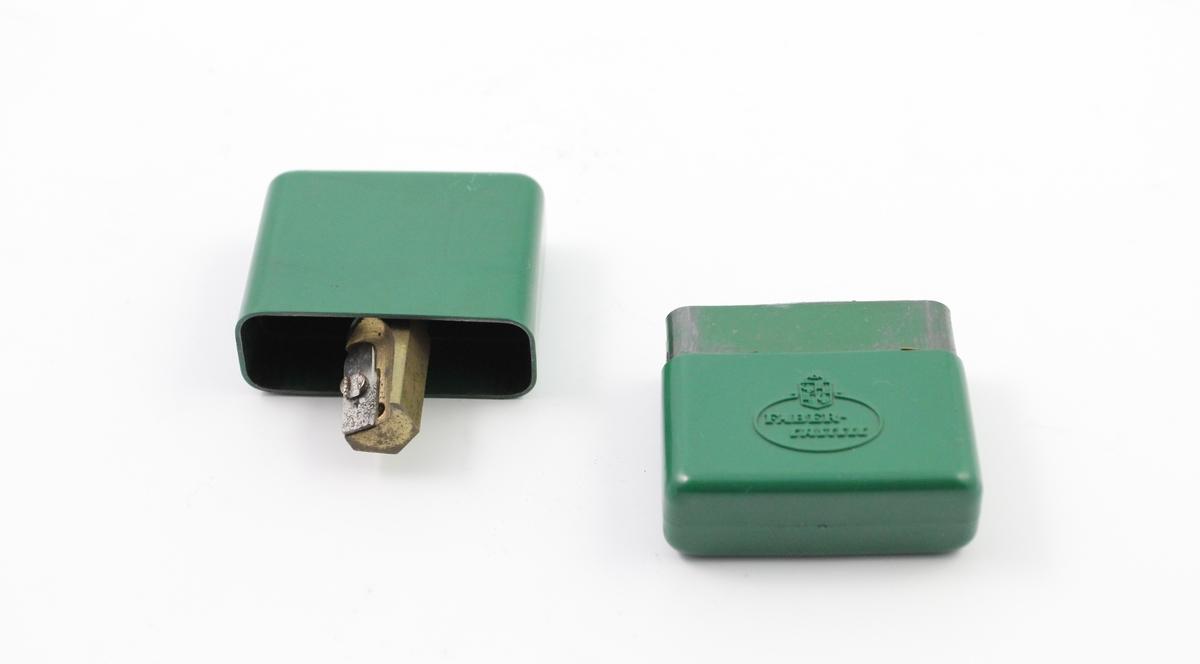 To kontorrekvisitter. A ukjent bruksområde med ligner en blyantspisser, B er en blyantspisser. Begge laget av grønn plast og nødvendig metall. A har sirkulær bunn, mens B har rektangulær bunn.
