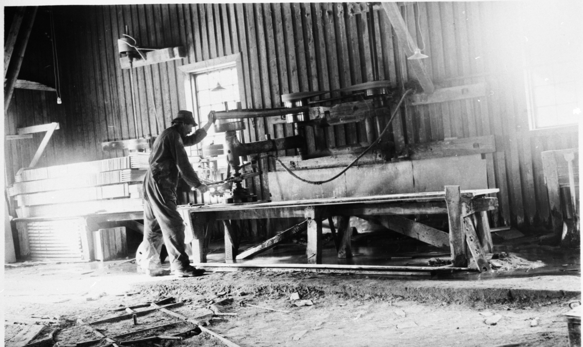 En mann står ved en maskin og arbeider ved Valdres Skiferbrud. Mannen er iført arbeidsklær og hatt.