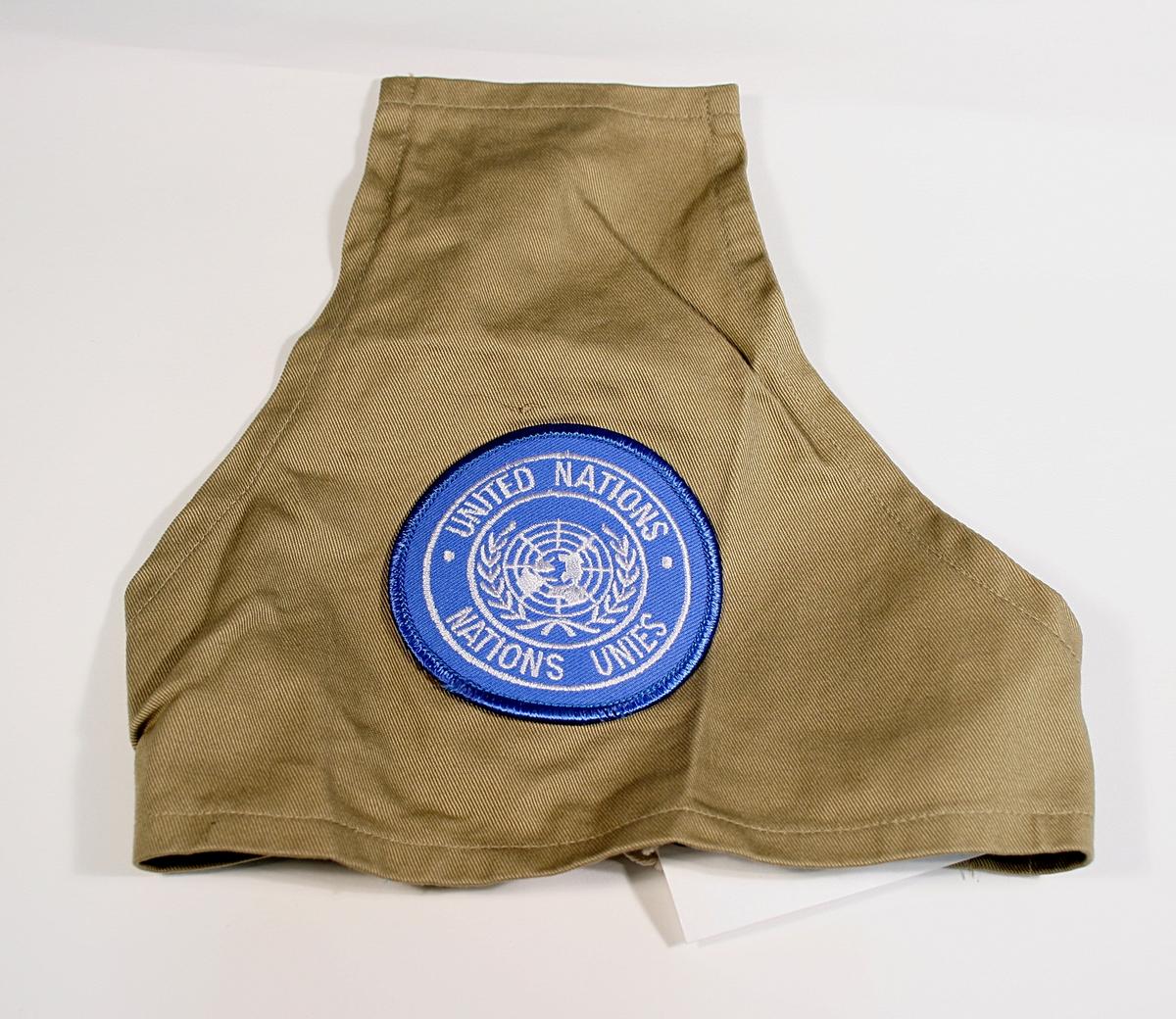 Trekantet skulderbind i beige bomull påsydd blått FN-merke. Bindet festes med strikk.
