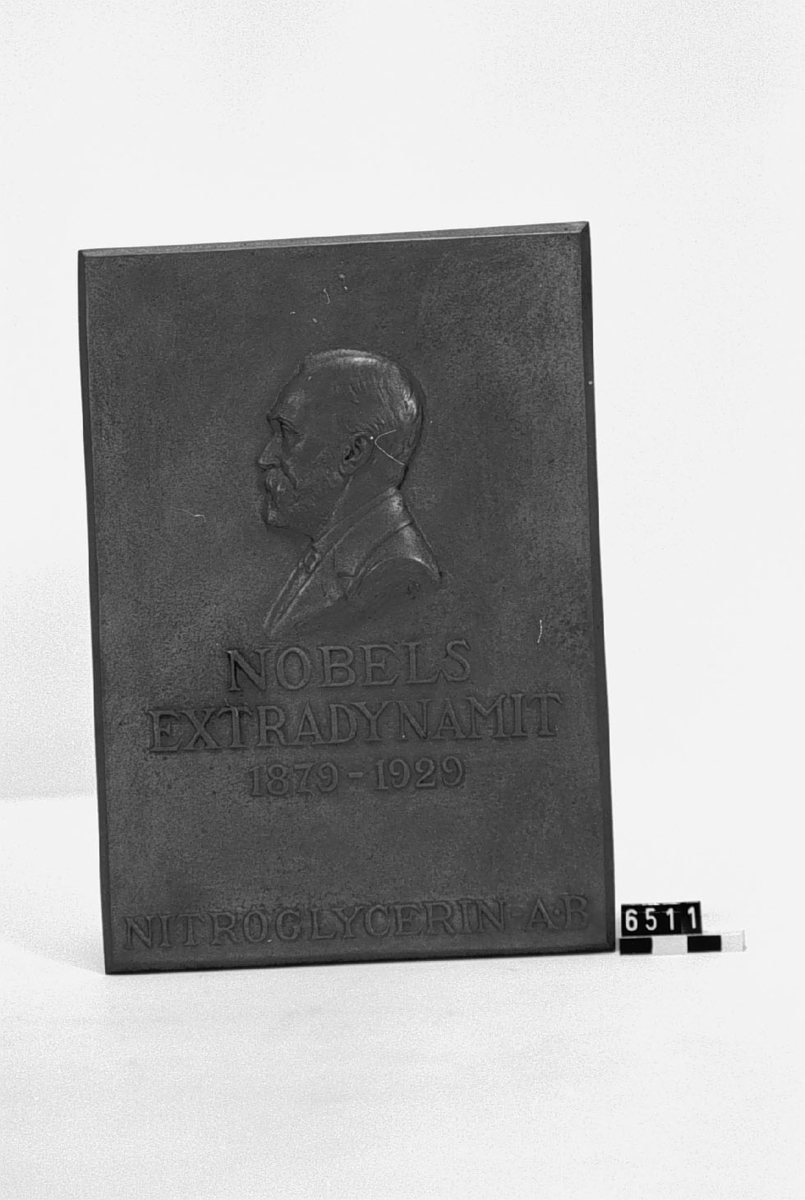 """Medaljong, över Alfred Nobel gjuten i koppar till minne av Nobels Extradynamits 50-årsdag. Med porträtt i relief av Alfred Nobel. Tillverkad 1929 för givaren. Text: NOBELS# EXTRADYNAMIT# 1879-1929# NITROGLYCERIN A.-B.""""."""