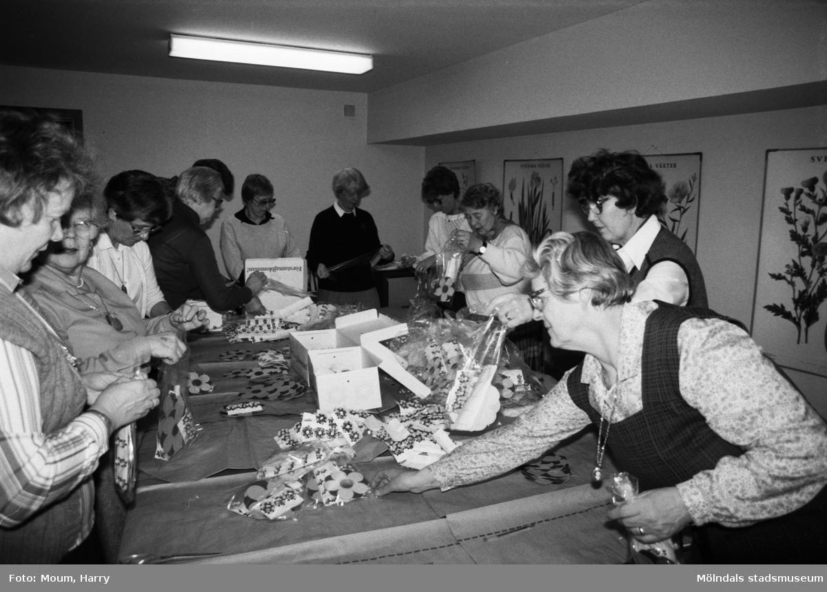 """Lindome förstamajblommekommitté, år 1984.  Fotografi taget av Harry Moum, HUM, för publicering i Mölndals-Posten, vecka 14, år 1984, med bildtexten:  """"Dags för Förstamajblomman  Det är snart dags för Förstamajblomman och i Mölndals kommun har vi bara en kommitté kvar och den finns i Lindome. På MP-fotografens HUM:s bild ses de flitiga damerna i Lindome i full verksamhet med förstamajblommor av olika storlekar."""""""