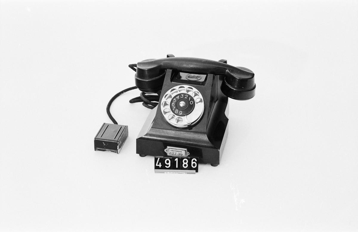 Telefonapparat BC 330, ändstationsapparat för AT-system. Bordapparat modell m33 av svart bakelit med fingerskiva av förnicklad mässing och textilklätt apparatsnöre anslutet til väggplint med lock av svartlackerad plåt.