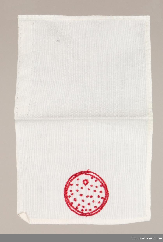 Bakduk med rött broderi i stjälkstygn och knutsöm föreställande brödkaka.