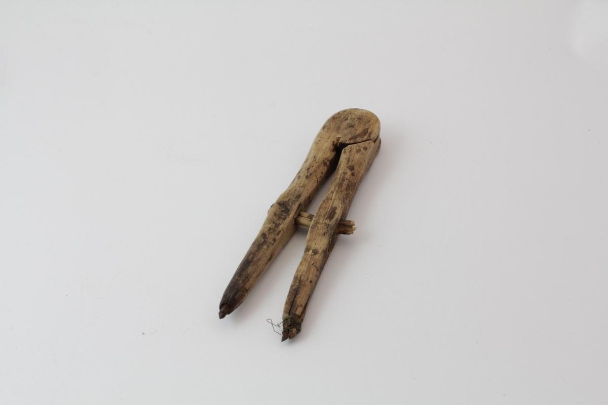 Passer som består av to bevegelige trestykker, klinket sammen i ene enden med en trenagle. En trebit er ført gjennom dem på midten, den er spikret til det ene benet, bevelig i den andre. Nederst er det banket inn to jernspisser.
