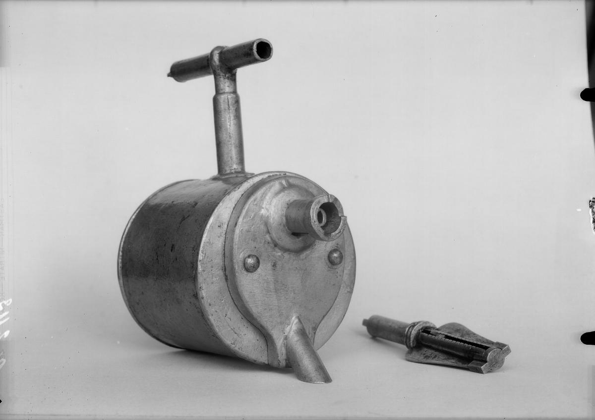 Christopher Polhems konstige tapp, av förtent bleckplåt med de fasta delarna nitade och lödda. Kugghjulet och dess hylsa, muffen på röret och ett foder i behållarens avlopp är av mässing. Att sätta i tunnor för avtappning av dyrbara vätskor t.ex. vin eller brännvin. För att monteras i tunna och mäta vätskemängden som tappas ut. Fungerade även som lås.