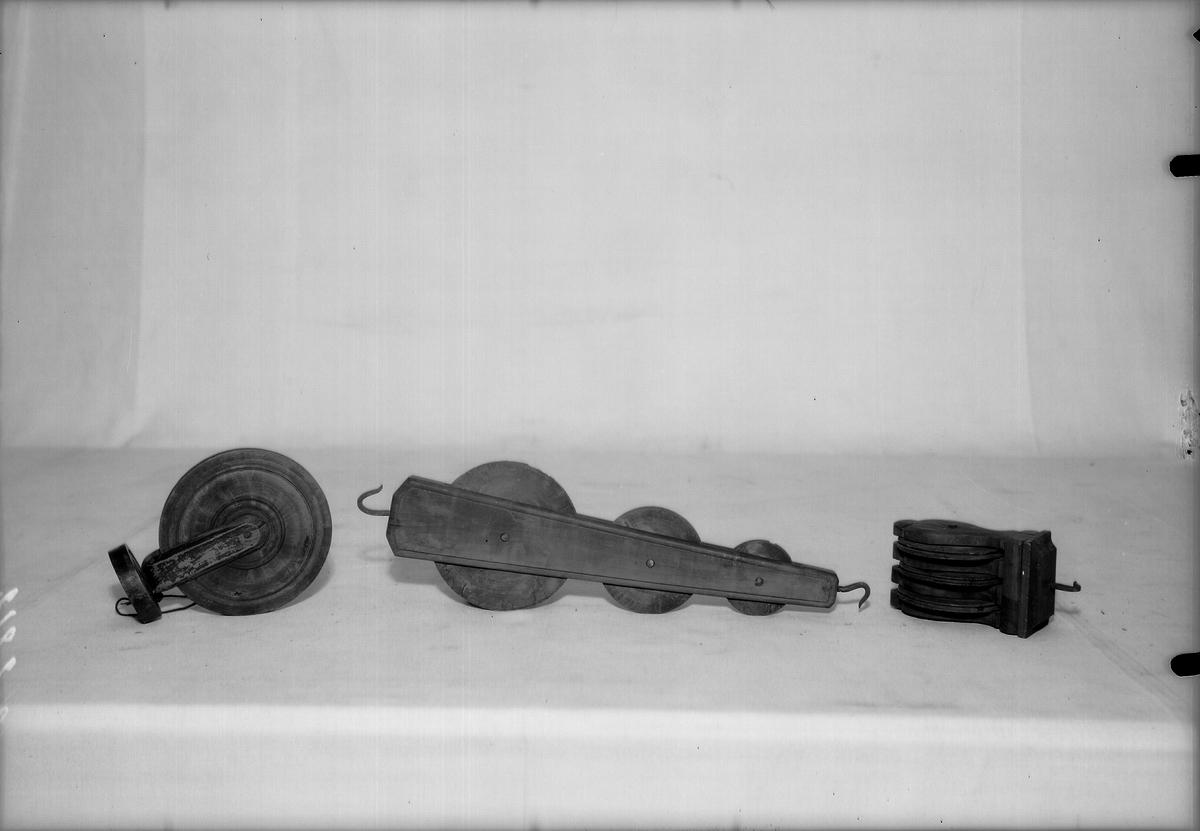 En samling drälltrissor av olika konstruktioner. Används för att hålla skaften i en vävstol vid vävning av dräll. Ersätter nickepinnarna som vanligen används när skaften inte är fler än fyra till sex st. Trissorna ser ut att vara av masurbjörk enligt fotot.  (Meddelat av Maria Brunskog, 1984-10-01).