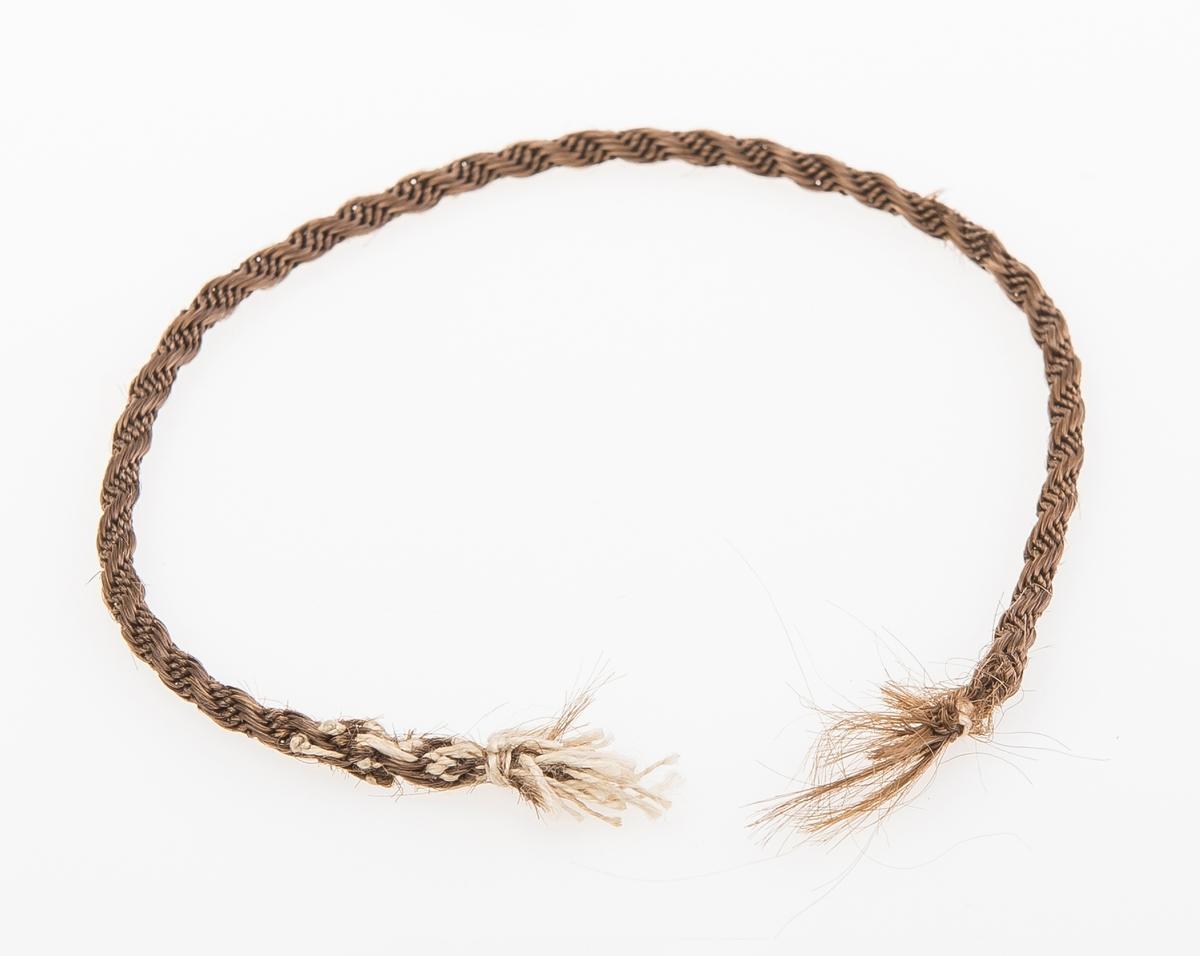 Lenke eller armbånd laget av brunt kvinnehår. Lenken er snodd, og det er festet hyssing i begge endene av lenken.