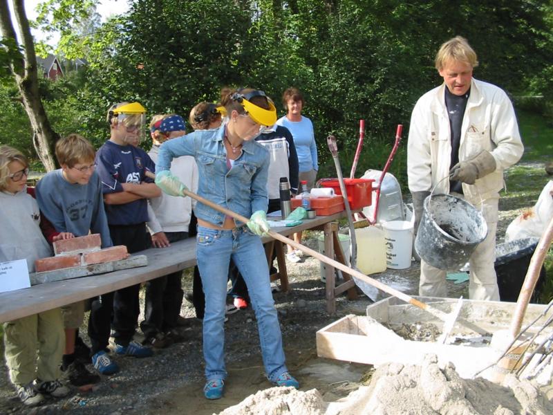 Her lærer barna å blande kalkmørtel til muring av kalkmur.