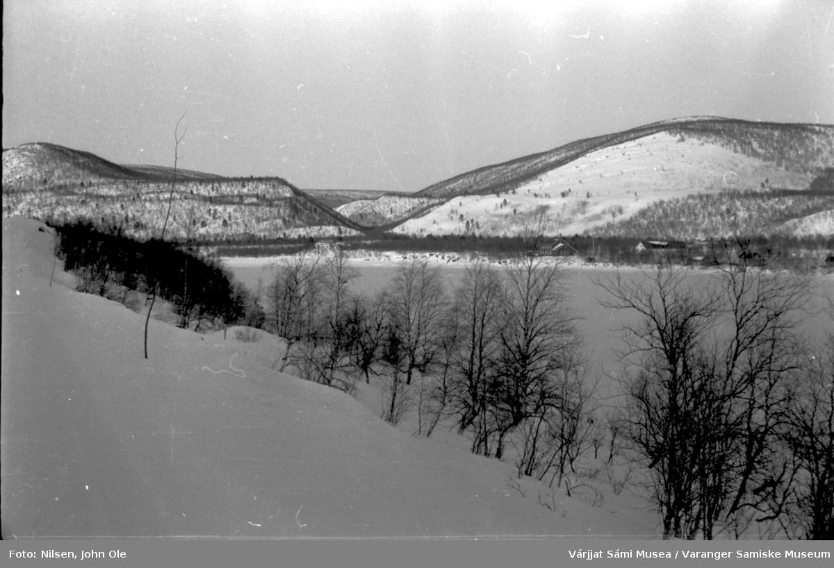 Snødekt vei, frosen elv eller vann, hus i bakgrunnen. Ukjent sted 23. april-1966
