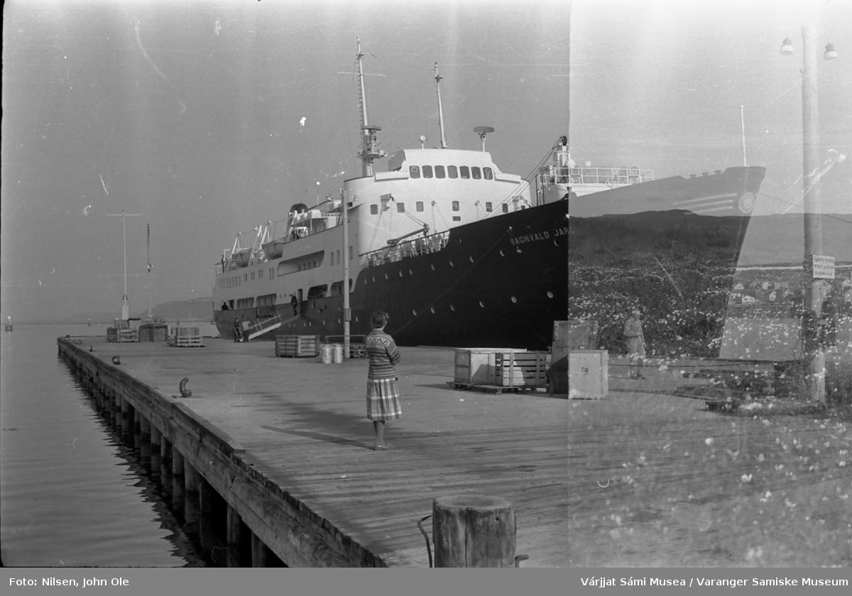 Hurtigruteskipet Ragnvald Jarl ved kai i Vadsø. Kvinnen som står og ser retning hurtigruta er Signe Nilsen. 20. juni 1966.