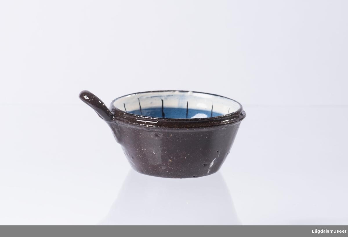 Kopp med dekorert innside. Dekoren er en blomst i bunnen av koppen og et ornament dekorert rundt toppen av koppen (på innsiden). Hanken er utformet for å kunne henge opp koppen.