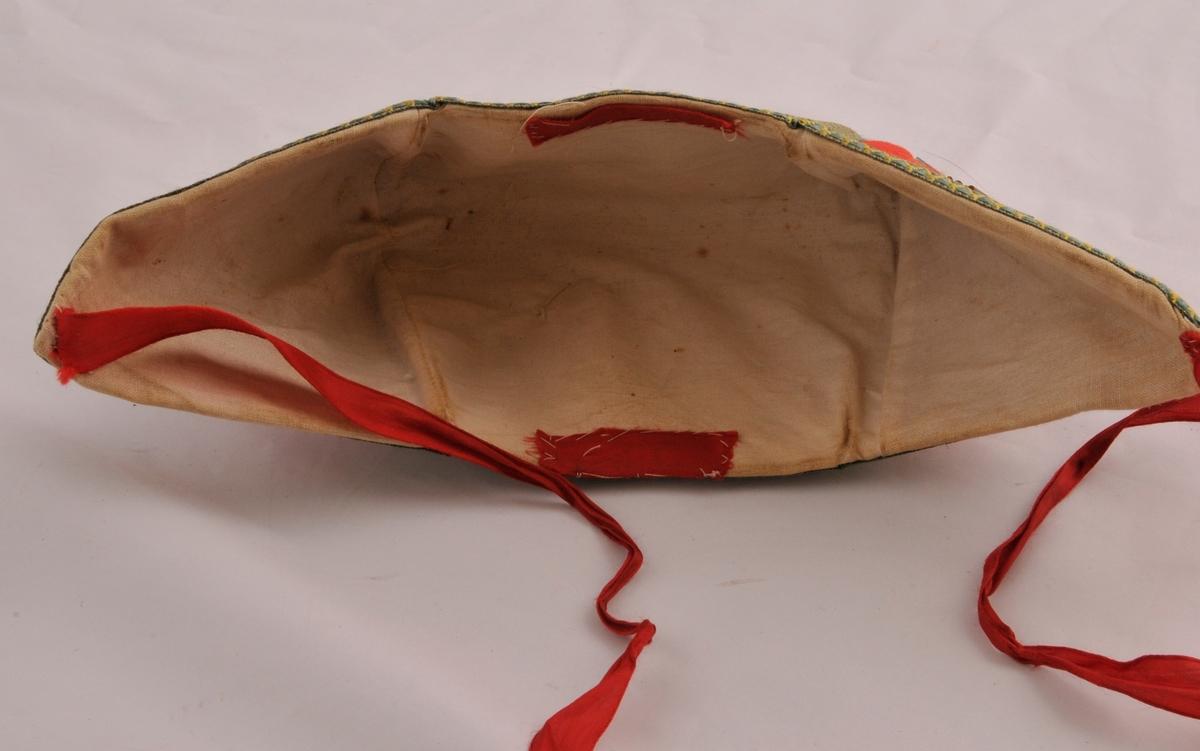 Trestykksluve i raudt ullstoff, med fór av tynt ubleika bomullstøy. Mellom ytterlaget og foret er det lagt inn eit stivt materiale (moglegvis papp eller tynn kartong). Luva er sydd saman med maskin. Eit lite stykke raudt silkeband midt framme og midt bak inni luva, sydd fast med kastesting. To hakeband av raudt silkeband, sydd fast med handsaum. Luva er dekorert med perlebroderi med åttebladsroser, sol-og korsmotiv med kvite,blå, gule,svarte,brune og grøne perler. Rundt alle kantar og stikningane på rettsida er der sydd på eit sikkskkmønstra band i grønt og gult.