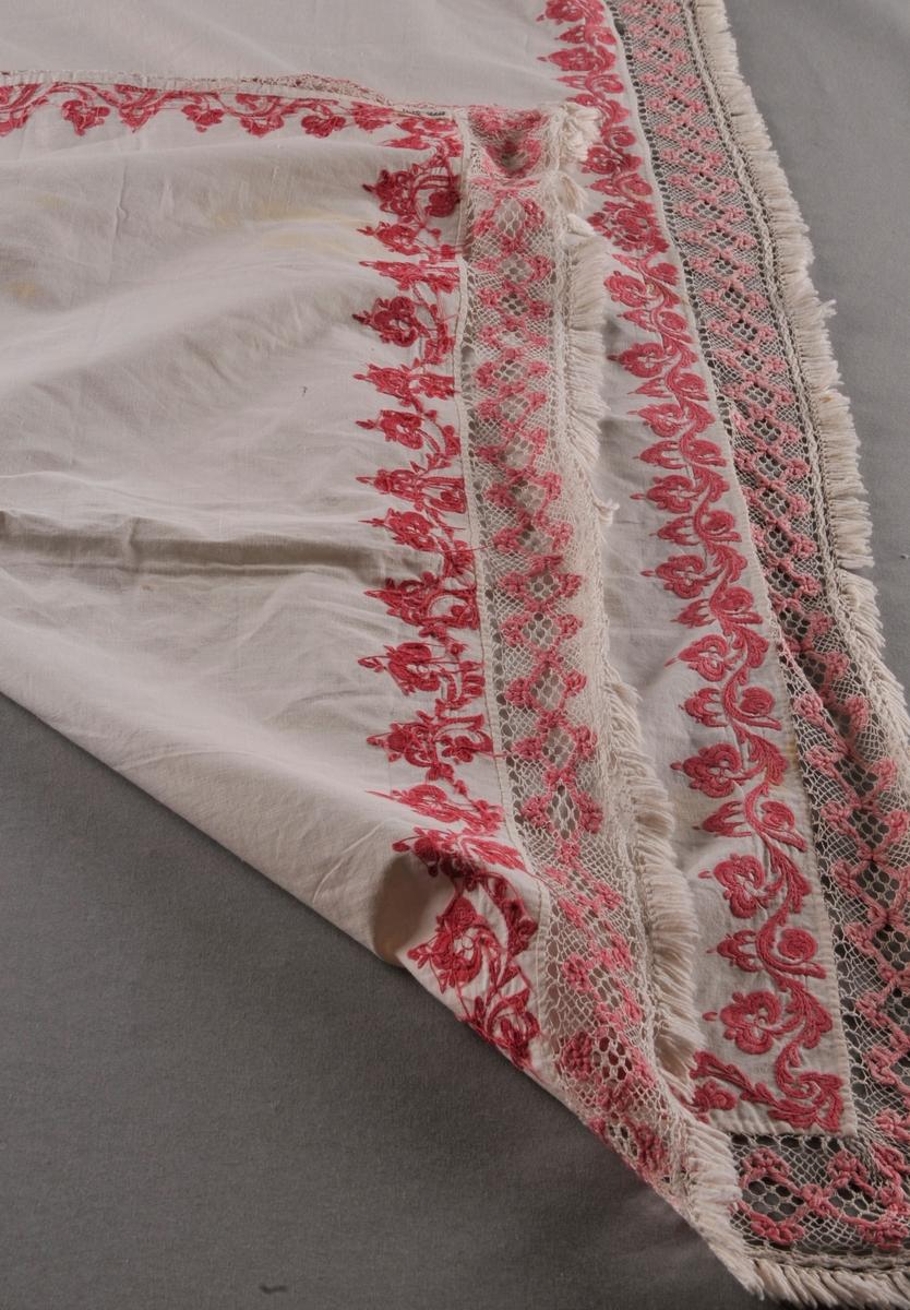 Rektangulært stykke av bomullslerret med rosa rosesaum kring alle sider. Ei påsauma kvit og rosa blonde i Telemarksbinding, i to ulike bredder, langs alle sidene.