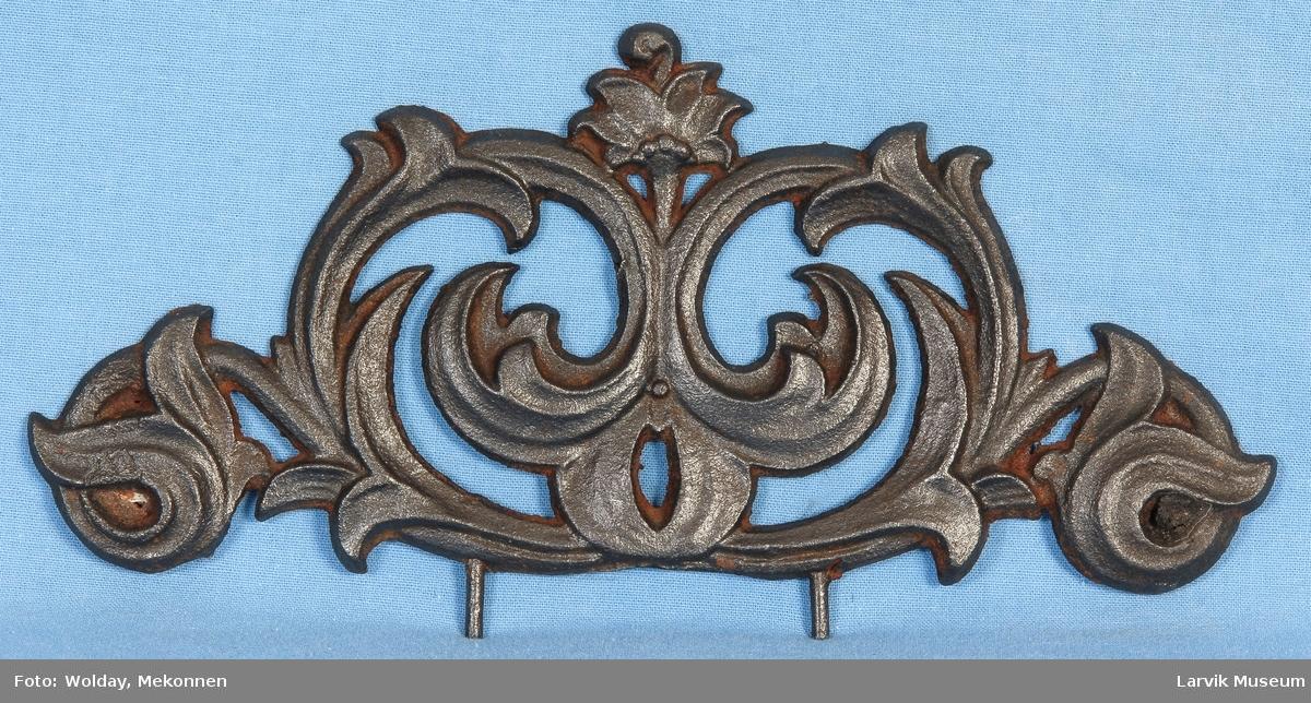 Bueformet. Gjennombrudt, ornamental krone. 2 tapper til feste i underkant