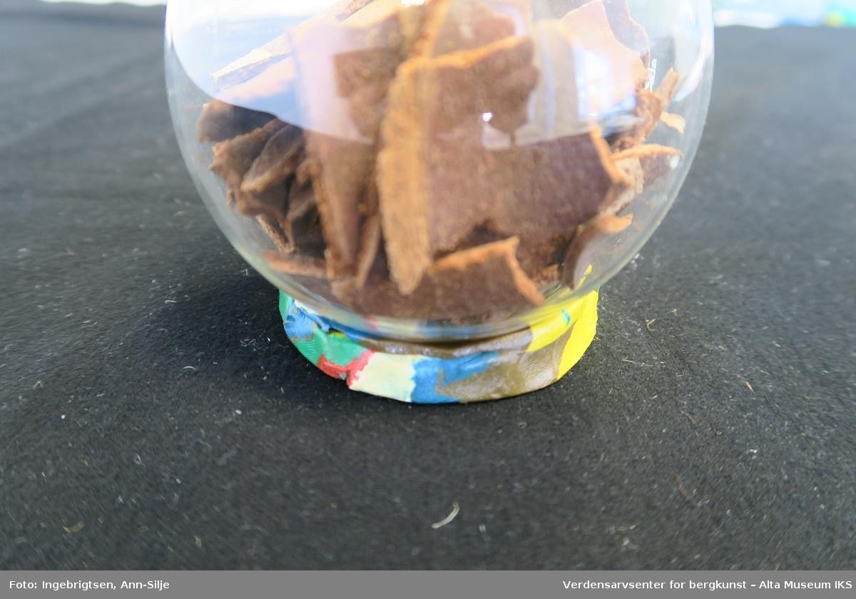 Teknikk: Flekkes, skrapes av trærne i sevjetida. Barksank.var en del av arbeidet i vedskogen Barken ble bært hjem i strisekker og tørket. Barken ligger i en glasskolbe som står på en sokkel av kitt.