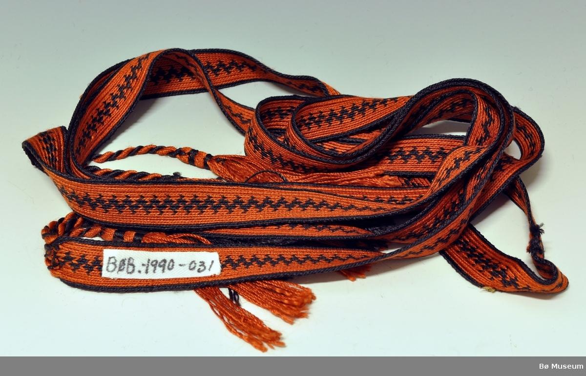 Langt hårbånd til bruk for å vippe håret. Hårbåndet er brikkebåndvevd.Renningens avslutning er delt i tre deler, hvor hver del er snodd og  frynser  avslutter hver del. I midten på hårbåndet er det en svart siksakmønstret bård, og på hver side av bården er det et bredt orange felt og et smalt svart felt.