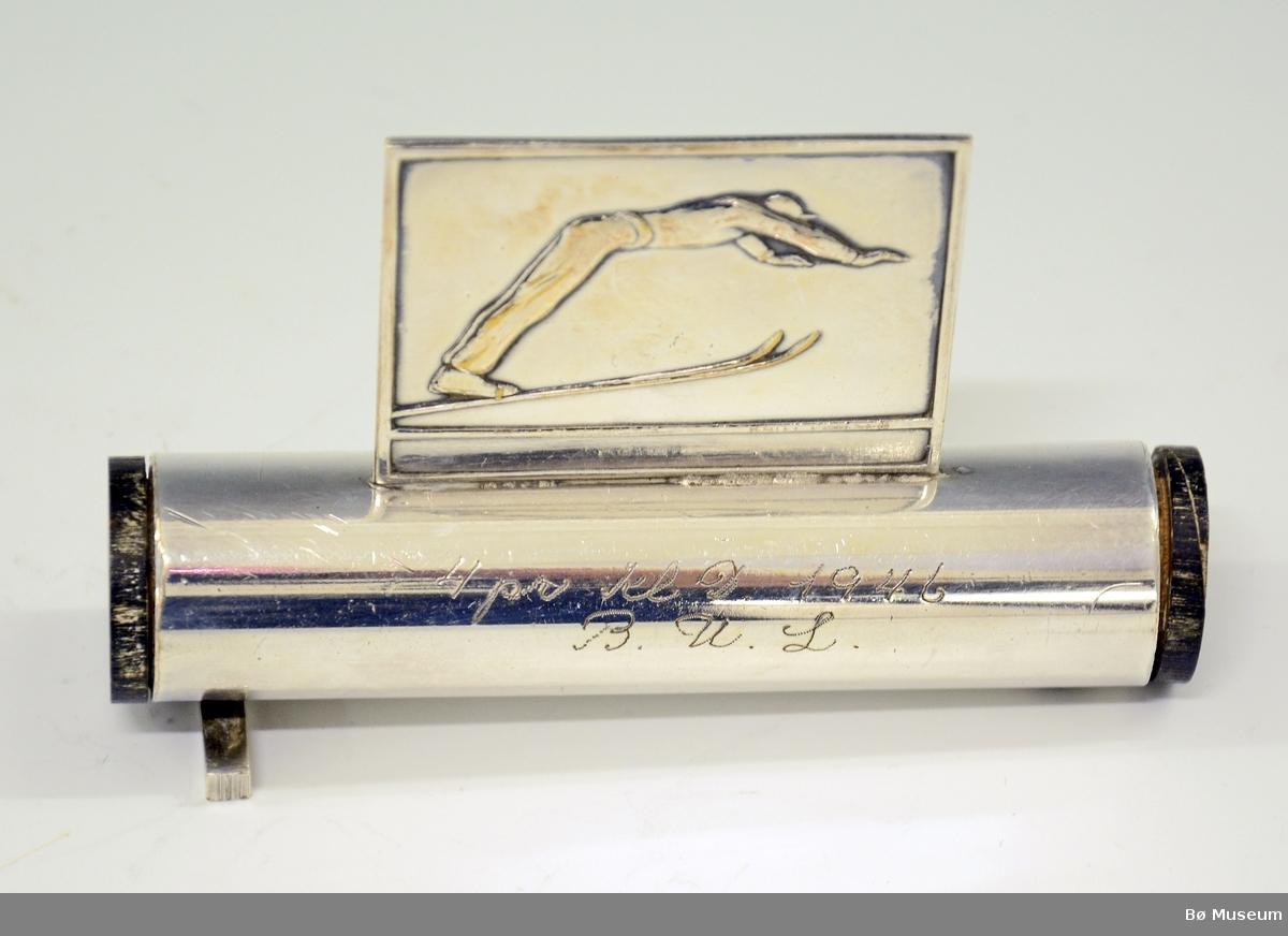 """Sølvetui - rund sylinder, med rektangulær sølvplate montert oppå. Kan være til f.eks. fyrstikker. Det er """"propper"""" av tre (sortlakkerte) i hver ende av sylinderen. Mangler en fot. Påskrift (gravert): """"4 pr. kl. D 1946. B. U. L."""" Stempel (under): Knut Larsen, Oslo. NM 14904."""