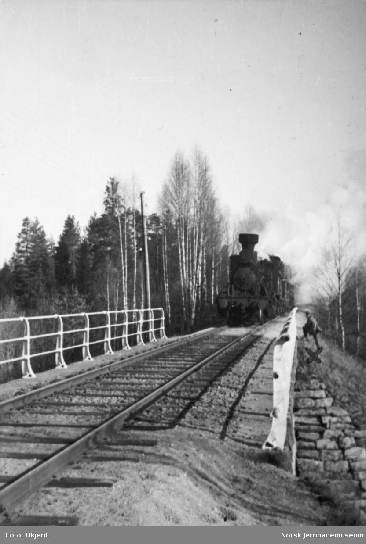 Damplokomotiv med tog ved bru på ukjent banestrekning