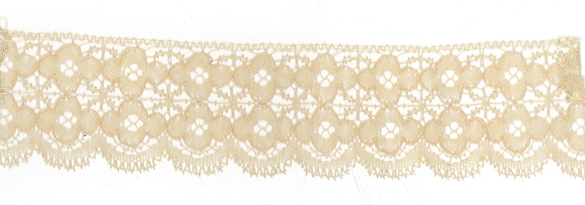 Teknik: Spetsen består huvudsakligen av 2 rader blommor arbetade i nätbotten med konturtråd. Uddarna är likaså arbetade i nätbotten och försedda med picot. I de mångsidiga fälten, som bildas mellan blommorna är mycket vackra figurer i flätning med picot.  Denna spets tillhör ryska samlingen.