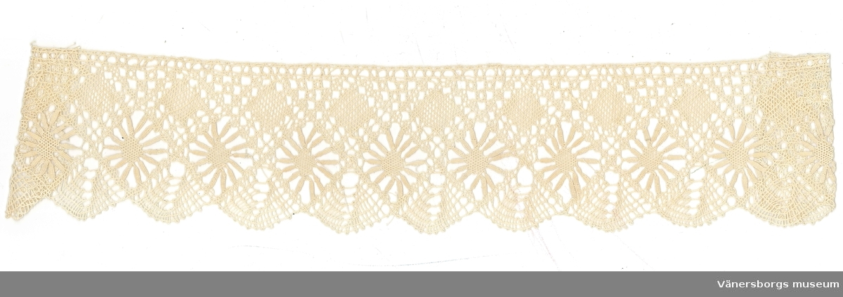 Teknik:Spetsen består av en rad nätbottnar, en rad blommor gjorda av mandlar och en mitt av nätbotten. Upptill kanten finns triangulära fält med rosenbottnar. Uddarna är arbetade i halvslag med långa slag.  Denna spets tillhör ryska samlingen.