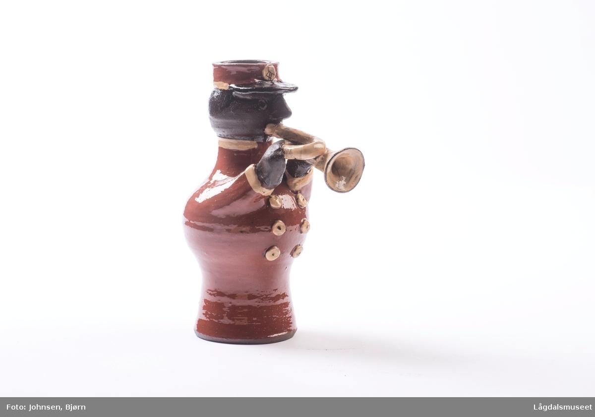 Dekoren på lysestaken utgjør uniformen til musikanten. Utforelsen er en musikant med messinginstrument.