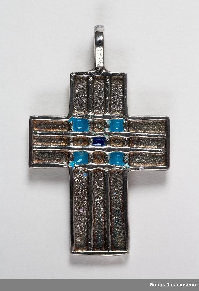 Hänge i form av ett kors, svagt välvt. Två streck i upphöjd relief längs korsarmarna som bildar ett rutmönster i mitten med dekor av turkos emalj. Silverstämpel och tillverkarens signatur på baksidan: BHN, Göteborgs stadsstämpel, 925, Y10.