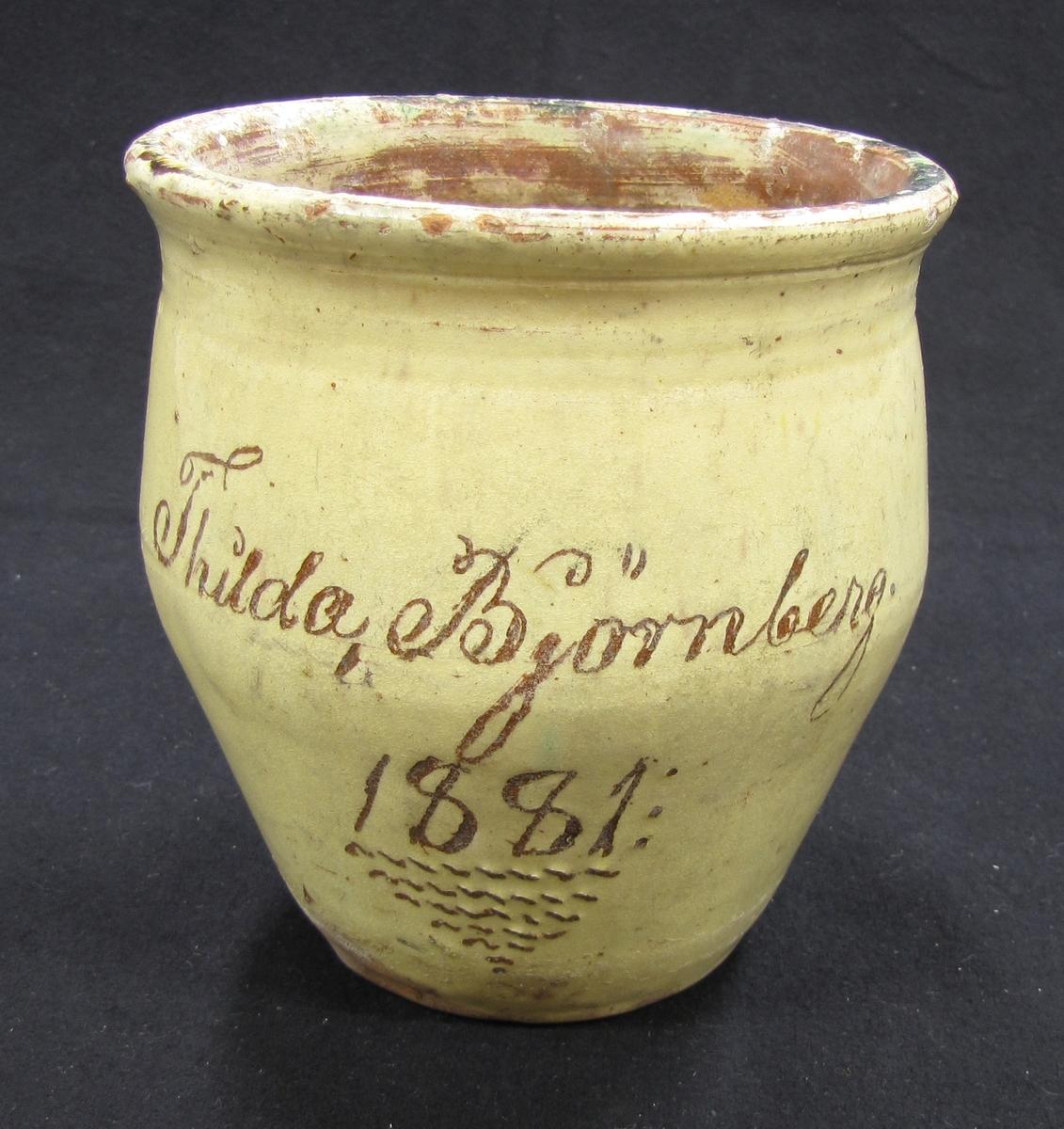 Blomkruka med gul glasyr och text i brunt: ''Thilda Björnberg 1881''