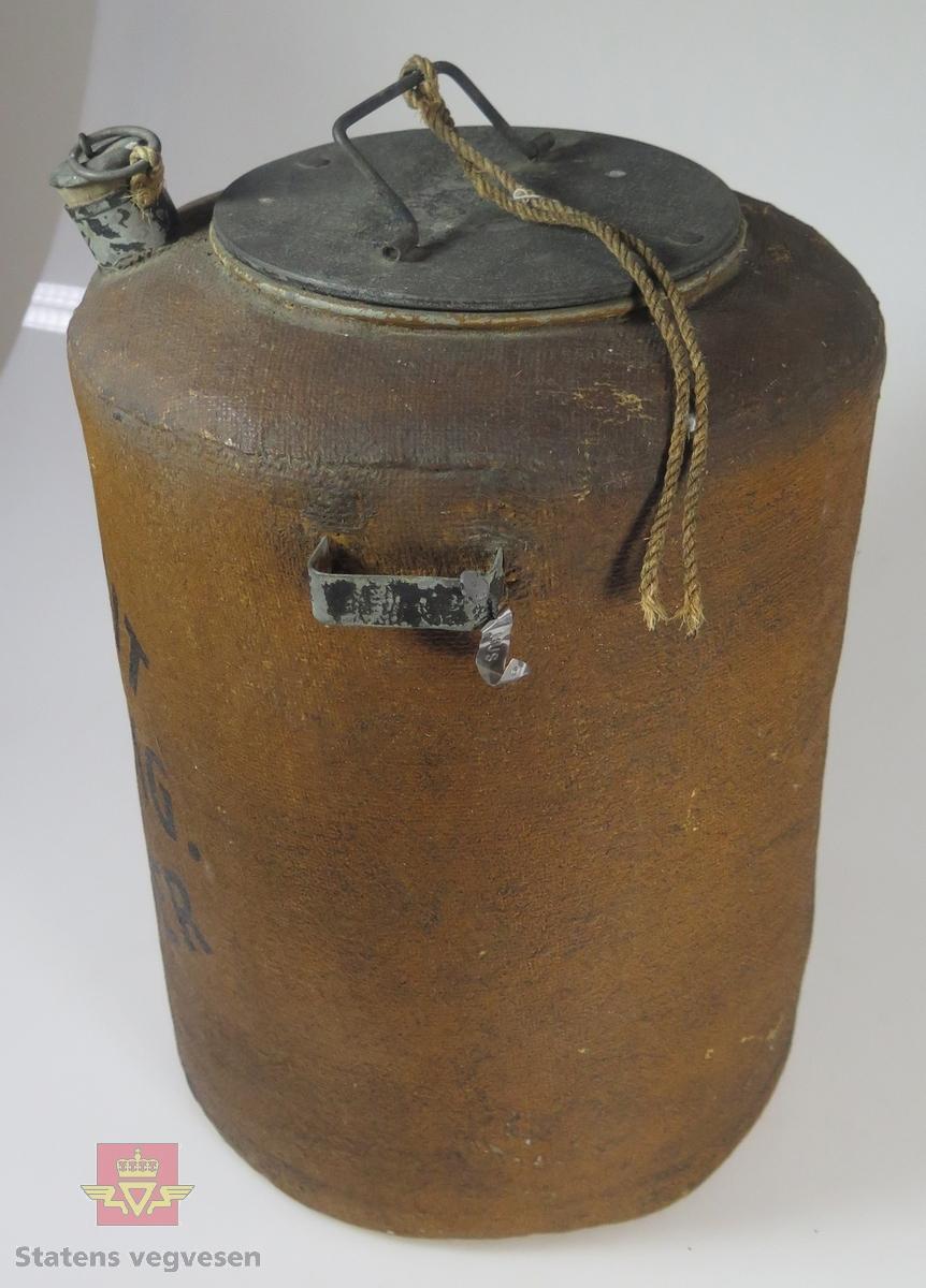 Sylindrisk beholder, (butt), av metall, (sink?). Har et rom med lokk, i senter, lokket er isolert med kork. Hulrom mot ytterveggen. Dette hulrommet har påfylling for varmt vann. Ytterveggen er isolert med brunfarget strie som har svart tekst. Beholderen har bærehåndtak.