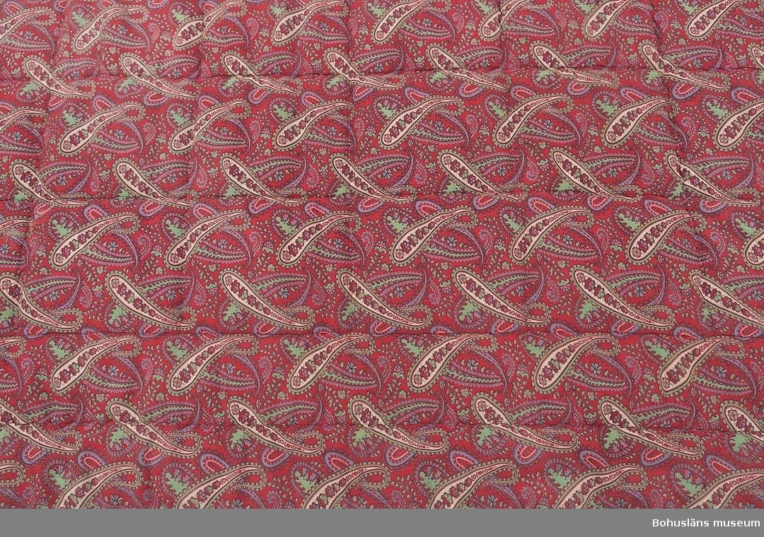 Så kallat stickat täcke med vadd som fyllning. Tryckt mönster med orientaliska smörjhorn på båda sidor. Många små hål; kvalitén på tyget är inte så hög.