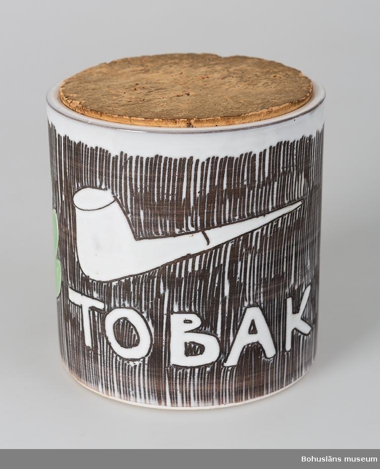 """Cylinderformad med dekor av vit, svart, grönt.  Text: """"Tobak"""" samt pipa och tre blad.  Målad signatur i botten: """"Nya SYCO Sweden Design Rune."""""""