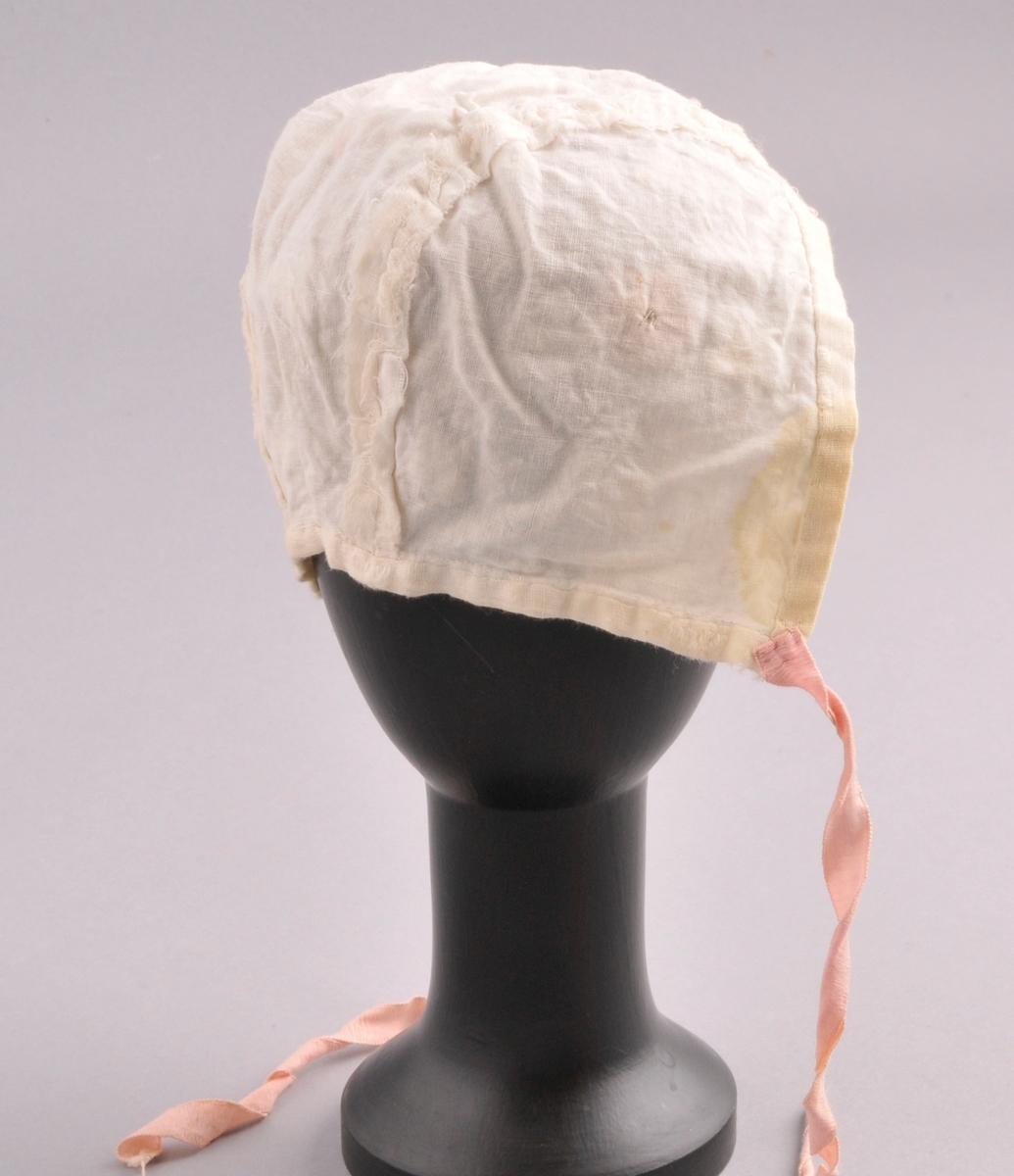 Luve av naturfarga voie, dekorert med broderte blomar, blomar av silkeband og silkeband lagt i faldar. Luva er sauma saman av tre delar. Luva har naturfarga for av bomull. Luva har to knytebånd. Sydd saman med maskin.