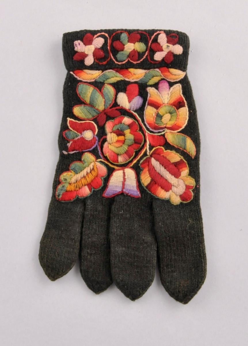 Svarte glattstrikka fingervottar med fleirfarga plattsaumsbroderi på handbaken og på oversida av mansjetten. Broderigarnet er tretråds, laustvinna og ikatfarga ullgarn.