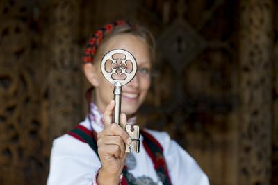 Kvinne i drakt viser nøkkelen til Gol stavkirke. Foto/Photo