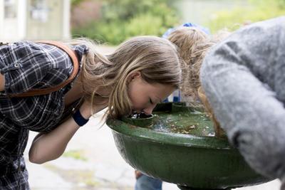 Tre ungdom drikker av vannfontenen i Gamlebyen