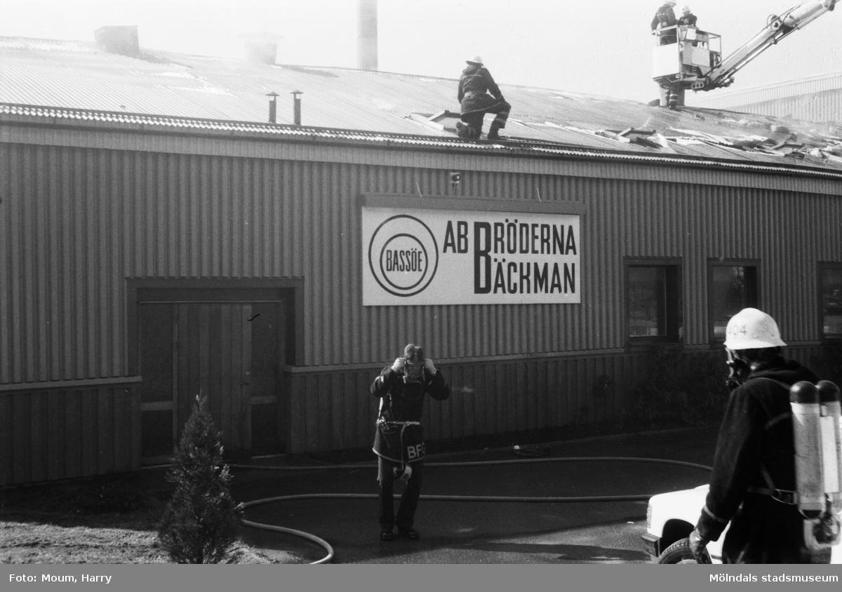 Brandkåren släcker brand i Bröderna Bäckmans industrilokal vid Gamla Riksvägen i Kållered, år 1984.  För mer information om bilden se under tilläggsinformation.
