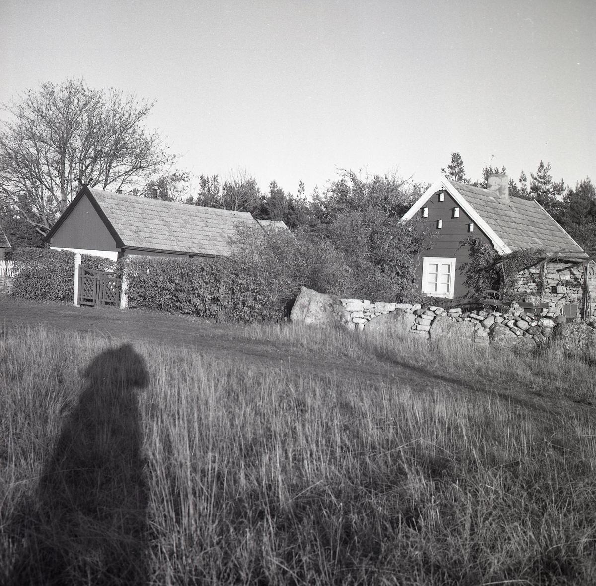 Ett bostadshus och en ekonomibyggnad bakom en stenmur i Lopperstad.