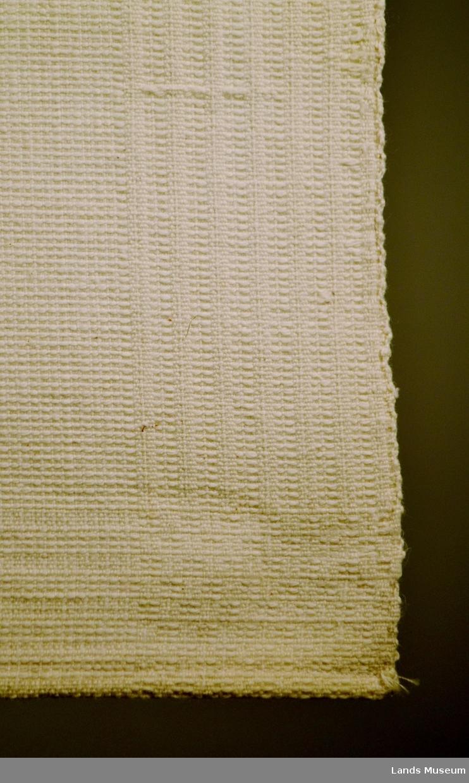 Håndkle til håndvak, hjemmevevet. Cryfarget tykt bomullsstoff. Fast vevet, mønstret i vev. Hempe påsydd.