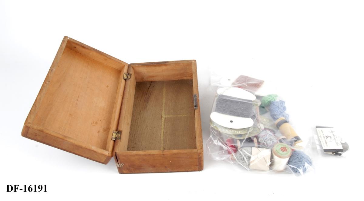 Skrin med lokk og nøkkelhull. I skrinet er det oppbevart sysaker som garnnøster, trådsneller, knapper og nåler.