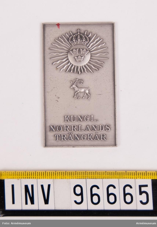 Plakett i silver för Norrlands trängkår. Stans nr 19922, härdad 1948-08-14. Plakett, 37x63 mm, åtsida m. kårens vapen, 3-kronor på rund sköld, krönt av kunglig krona, jämte strålar samt därunder ren, nedtill inskription KUNGL. NORRLANDS TRÄNKÅR, plaketten omgiven av upphöjd kant.