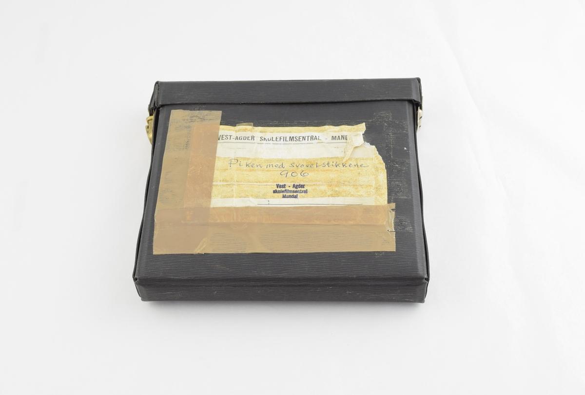 Filmrull i eske. Film på metallspole. Firkantet papir etui åpnes langs en av sidekantene, festes med metallspenne.