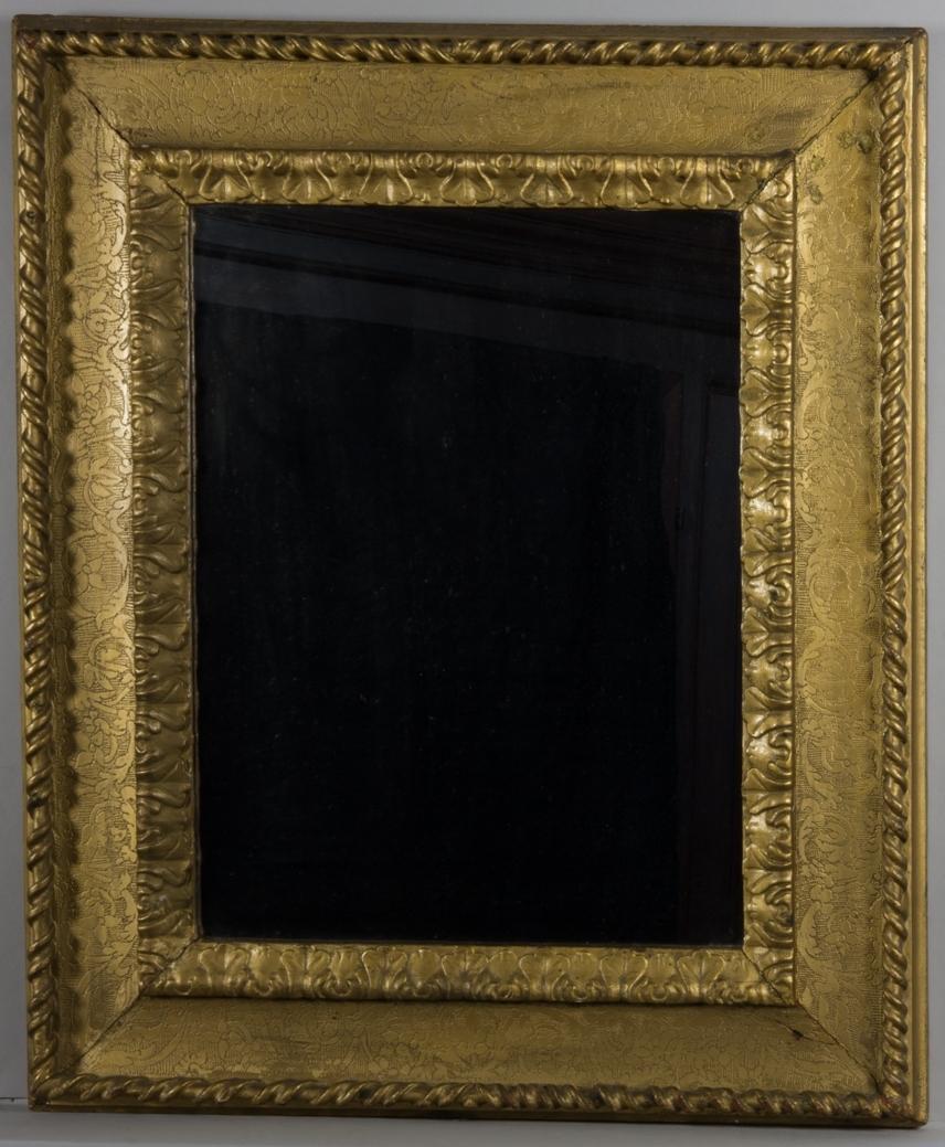 Spegel, stående rektangulär, med guldfärgad träram. Dekorerad med ytterst bandomslingrad stav, växtslingor mot bakgrund av tättställda punkter, sgraffitoliknande och innerst skulpterad växtornamentik.