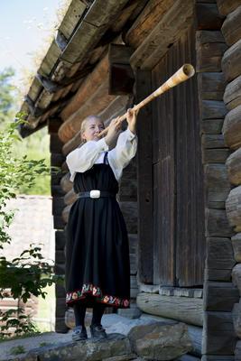 Kvinne i drakt spiller på lur i Friluftsmuseet