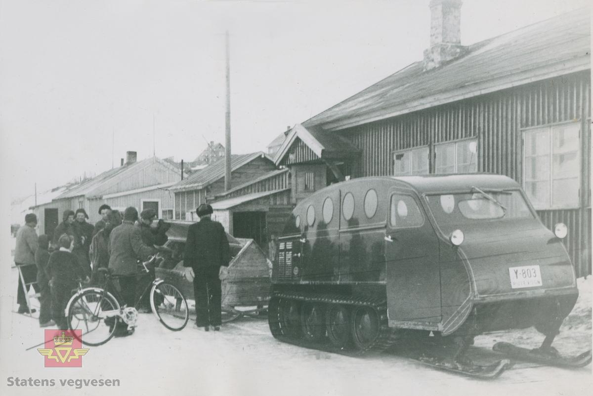 """""""Bombardier Snowmobil brukt som skolebuss i Trøndelag."""" I følge merking i album. Her også med tilhenger. Kjennemerke på snowmobilen er Y-803 Rutevogn.  """"I de enkle brakke-lokalene på Bjølsen ble snowmobilene satt sammen og klargjort. På det som nå er fotballbaner midt i Oslo, ble de merkelige kjøretøyene prøvkjørt."""" Samme bilde og tekst fra """"Familiefirmaet-utenom allfarvei/2000 årsboken."""" Colbjørnsen & Co A/S, av Bjørn Ausjen Johannessen. Sannsynligvis er bildet tatt i Trøndelag.   30.01.2018: """"Beltebilen er registrert Y-803 (Finnmark). Finnmark Fylkesrederi og Ruteselskap (FFR) hadde en Bombardier, typer R-28, 1958-modell. Vi ser av skiltet at den er registrert som """"Rutevogn"""". Beltebilen hadde 13 sitteplasser. Det spørs om beltebilen hadde blitt utlånt til Trøndelag. FFR brukte tidligere beltebiler på enkelte strekninger vinterstid"""".  Opplysninger fra Sveinung Berild.  Norsk vegmuseum har også en beltebil produsert i 1951 av firmaet Bombardier Ltd i Canada. Forhandler i Norge var Colbjørnsen & Co. Snowmobilen er omtalt i Anleggsmaskinen """"Maskinelt tilbakeblikk"""" Nr. 12 -2011: side 72-73, """"Snøbilen -beltegående 60-åring."""" Se gjenstandsnummer NVM 00-G-02172."""