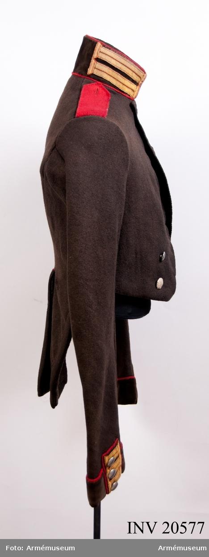 """Grupp C I. Av svart kläde. Axelklaffar av rött kläde med svart underkläde, fastsydda i ärmsömmen och fastknäppta med en knapp av vit metall. Foder av grov linnelärft. Dubbelknäppt med 6 flata knappar av vit metall på varje sida. Krage av svart sammet med röd passpoal på övre och nedre kanten (den nedre  kanten kallas """"lärdekant"""" och infördes för ryska specialtrupper år 1816). På kragen två knapphål av gult redgarnsband. Kragen är fodrad med svart kläde och sammanknäppt med tre hyskor och hakar. Skörten har passpoal av rött kläde. Ärmuppslag av svart sammet med uppslagsklaff av svart kläde. På övre kanten och kring uppslagsklaffen passpoal av rött kläde. På uppslagsklaffen tre knapphål av gult redgarnsband med tre knappar av vit metall. LITT  S Savage, kejserliga ryska armén, S Petersburg, Sida 8. Livgardets Sapeurbataljon grundades 1812 och användes intill år 1817 denna frack. År 1817 fick bataljonen en frack med revär, sammanfäst med hakar på bröstet. B Söderblom, Livgardets 2. artilleribrigads historia, S Petersburg, 1898, sida 80. F von Stein, Geschichte des russischen Heeres, Hannover, 1889, sida 277: Lärdekant."""