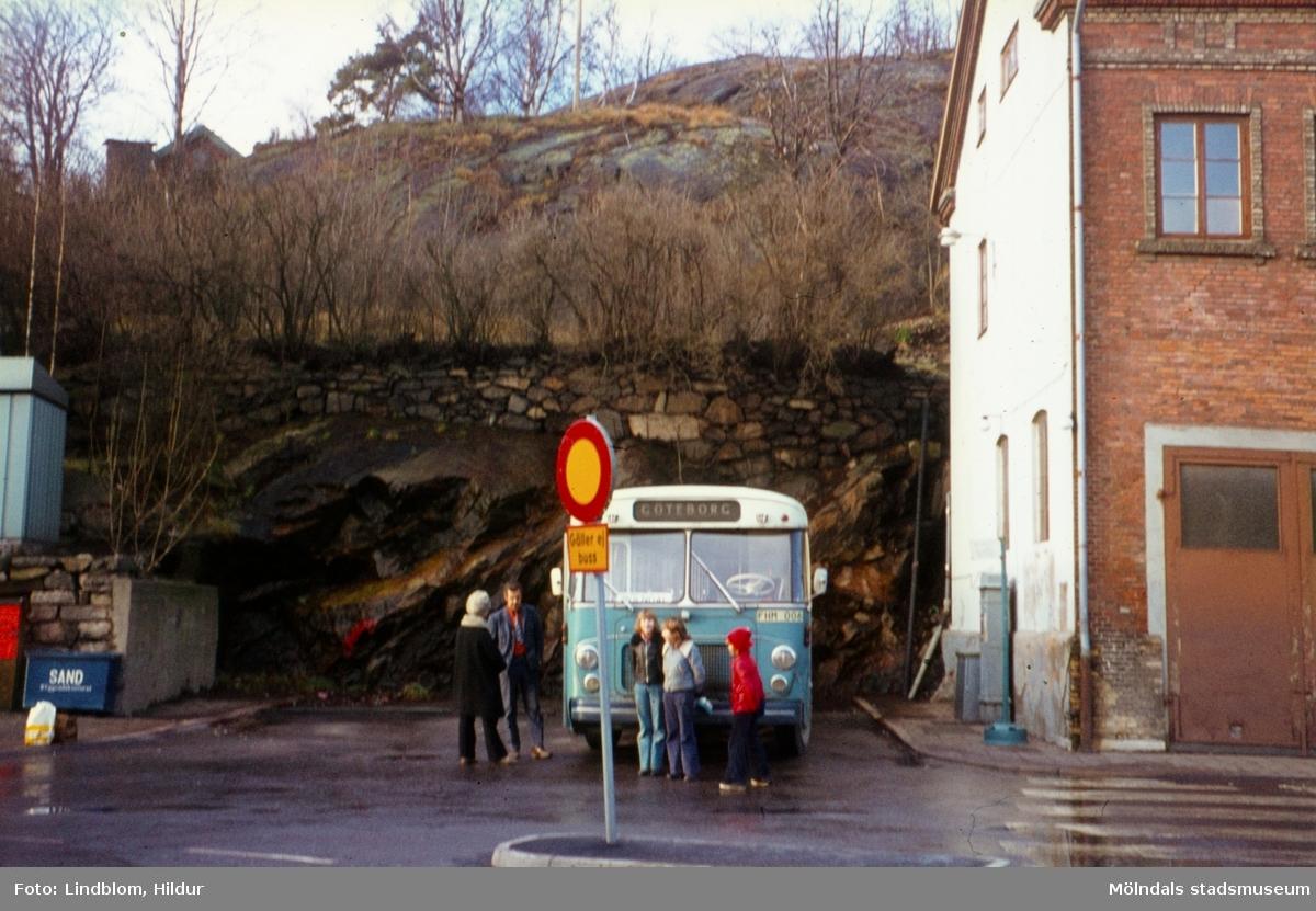 En samling människor står vid en blå buss på en busshållplats vid Gamla Torget i Mölndal, 1970-tal. Till höger ses del av huset Kvarnbygatan 41, tidigare brandstation och garage för polisbilar, numera Mölndals målarskola.  För mer information om bilden se under tilläggsinformation.